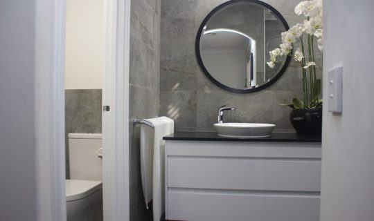 small bathroom renovation with round mirror modern
