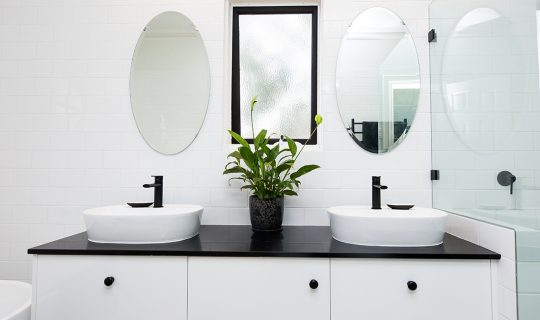 black and white sinks with oval mirrors above