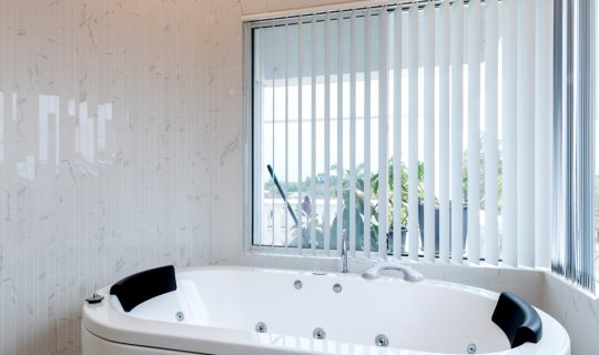 large spa bath with venetian blinds behind