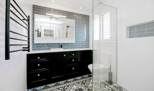 black sink with tiled floor and towel rail
